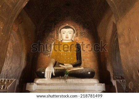 Ancient architecture of old Buddhist Temples at Bagan Kingdom, Myanmar (Burma). Golden Buddha statue inside one of pagoda ruins - stock photo