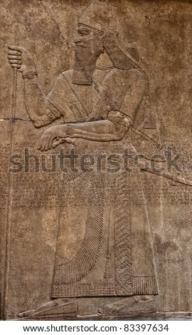 Ancient assyrian clay relief depicting a warrior with a sword and text written in cuneiform writing - stock photo