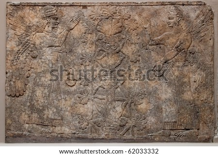 Ancient assyrian relief depicting winged gods or spirits and a tree - stock photo