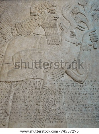Ancient Assyrian wall carvings of a man and cuneiform writing - stock photo
