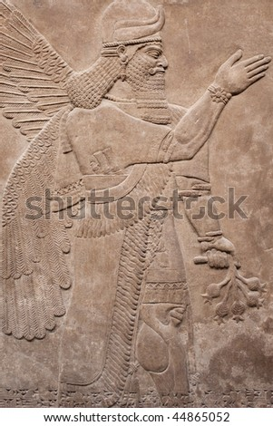Ancient assyrian winged god carved in stone - stock photo