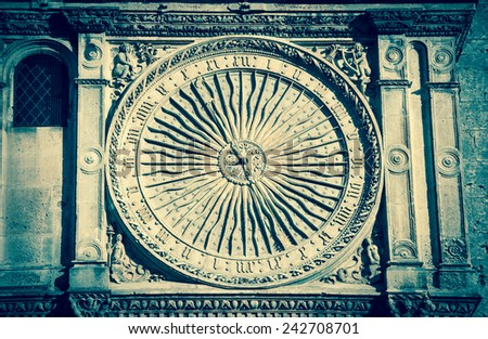 Ancient astronomical clock in Sun shape on the facade of famous Chartres cathedral (France). Aged photo. - stock photo