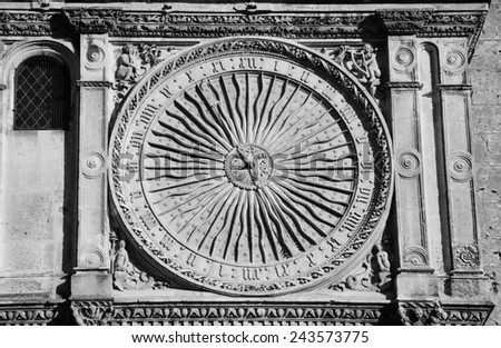 Ancient astronomical clock in Sun shape on the facade of famous Chartres cathedral (France). Aged photo. Black and white. - stock photo