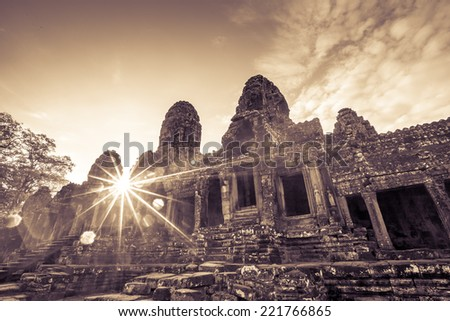 Ancient Bayon castle with sun ray in Angkor Thom, Cambodia.  Retro filter. - stock photo