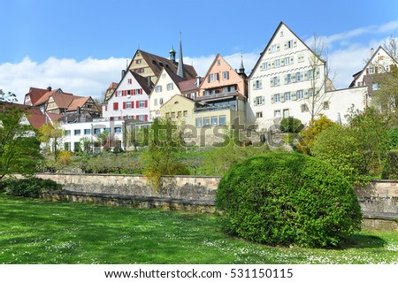Ancient blocked residential buildings, located along the quay. Lush greenery in the foreground. Bietigheim, Baden-Wurttemberg, Germany.