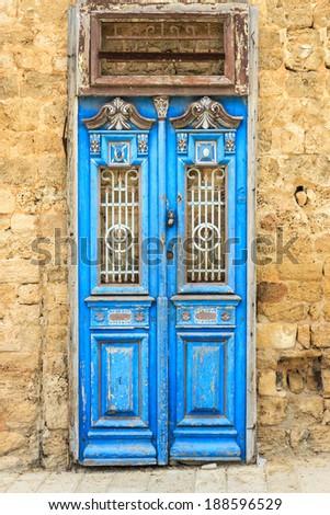 Ancient blue door in mediterranean city - stock photo