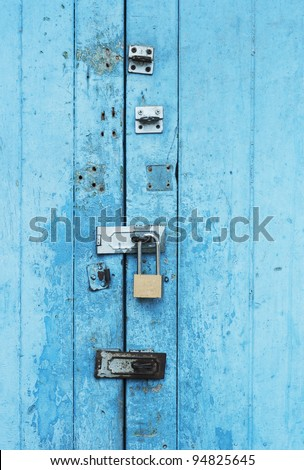 ancient blue door with iron door locked - stock photo