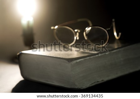 Ancient book lit by candle and old glasses on top - stock photo