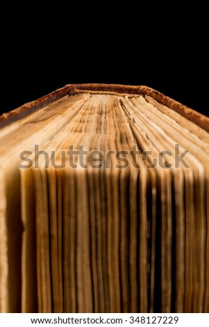 ancient book shot on black background. The book is in bad condition. - stock photo