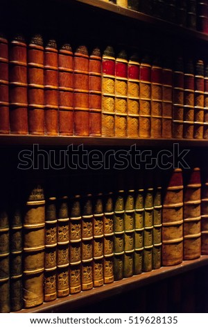 Ancient books on wooden shelf.