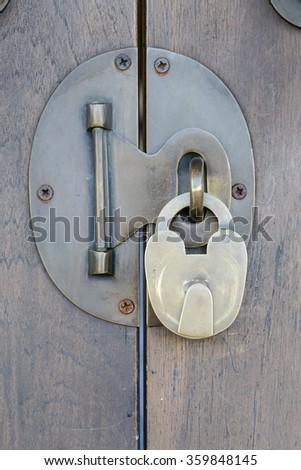 Ancient brass lock on wooden door with handle - stock photo