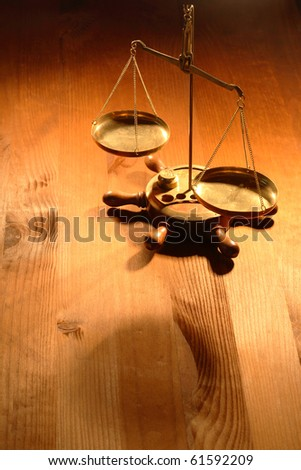 Ancient brass weight scale standing on nice wooden background - stock photo