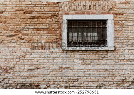 Ancient brick wall texture. Window with grill and railings. Venice italy - stock photo