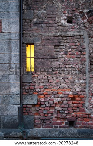 Ancient brick wall with small lit window - stock photo
