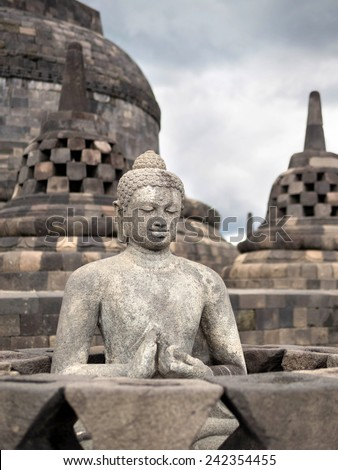 Ancient Buddha statue at Borobudur Temple in Yogyakarta, Java, Indonesia. - stock photo