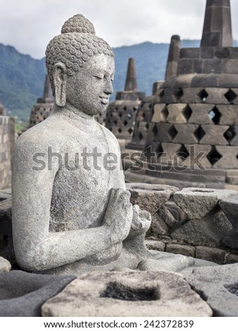 Ancient Buddha statue at Borobudur Temple ruins in Yogyakarta, Java, Indonesia. - stock photo