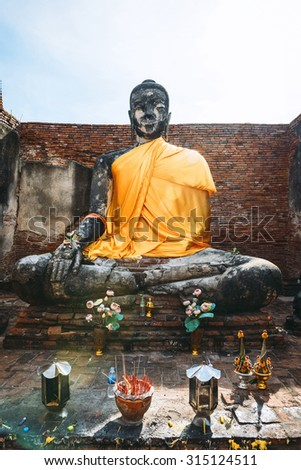 Ancient Buddha statue with shiny yellow robe, in Ayutthaya, Thailand - stock photo