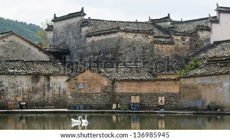 ancient buildings with reflection in the center pond in Hongcun village, Anhui, China. Hongcun village is selected as world heritage, famous for its well protected ancient Chinese style buildings. - stock photo