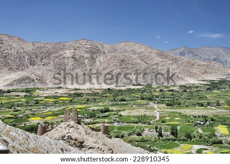 Ancient castle among lush green oasis village - stock photo