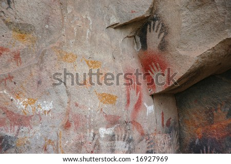 Ancient cave paintings of Patagonia, with human hands and animal hers. - stock photo