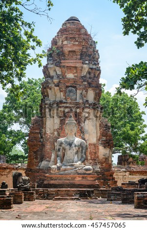 Ancient cement buddha statue in front of ruined pagoda at ancient temple in world heritage city of Ayutthaya, Thailand - stock photo