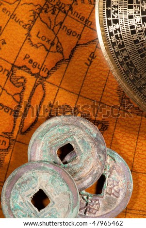 Ancient Chinese coins and compass (Luo Pan) over antique map