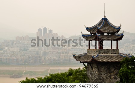 ancient chinese pagoda overlooking yangtze river against a modern skyline - stock photo