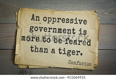 Ancient chinese philosopher Confucius quote on old paper background. An oppressive government is more to be feared than a tiger.  - stock photo