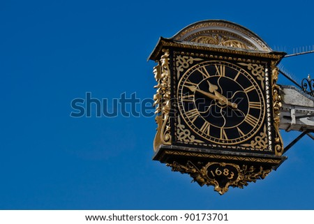 Ancient clock over blue sky. Guildford, Surrey, Great Britain. - stock photo