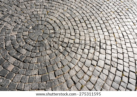 Ancient cobblestone paved circle on the pavement under the sunlight