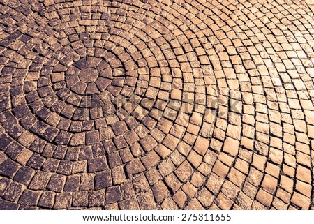 Ancient cobblestone paved circle on the pavement under the sunlight. Image in the orange-purple toning