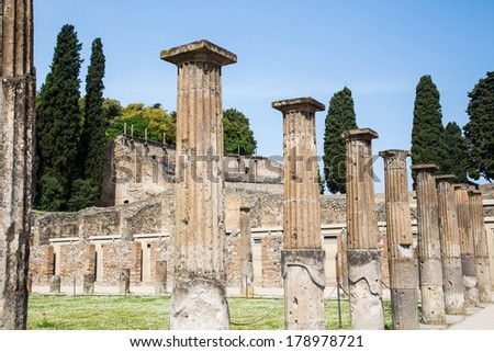 Ancient columns by grass lawn with cypress trees in Pompeii