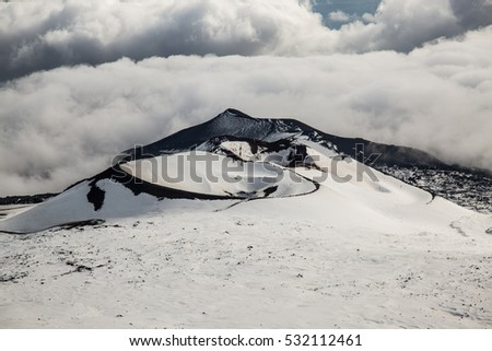 Ancient craters of the volcano Etna covered by snow