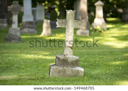 Ancient cross grave marker in cemetery - stock photo