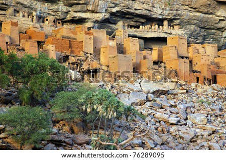 Ancient Dogon and Tellem houses on the Bandiagara escarpment in Mali with trees - stock photo
