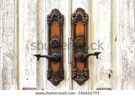 Ancient door handle on white old wooden door background - stock photo