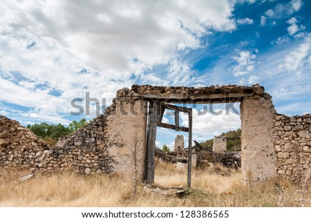 Ancient door in a stone wall, entrance to an old house - stock photo