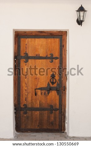Ancient door with a lamp - stock photo