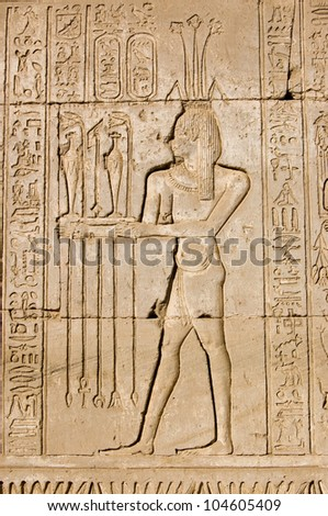 Ancient Egyptian hieroglyphic carving of a priest making an offering to Hapi, the god of the Nile.  Shown by the lotus on his head.  Outer wall of Dendera Temple, near Qena, Egypt.