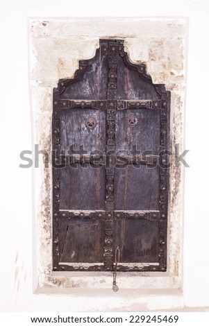 Ancient elaborately decorated Indian wooden door set in a white washed wall - stock photo