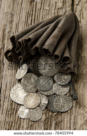 Ancient English silver coins spilling out of a leather purse on an oak table