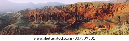 Ancient formaions panoramic view, Clay desert, Red hills, Konorchek canyon, Kyrgyzstan, Central Asia. Artistic filtered image. - stock photo