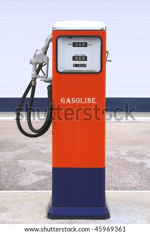 Ancient gas pump painted in bright dark blue and orange in the setting of an old gas station
