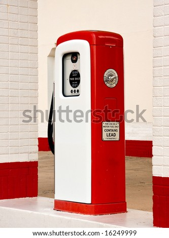 Ancient gas pump painted in bright white and red in the setting of an old gas station - stock photo