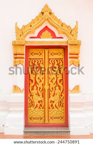 Ancient Gold carving wooden door of Thai temple. - stock photo