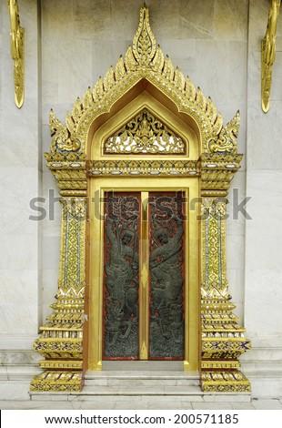 Ancient Golden carving wooden door of Thai temple in Bangkok, Thailand. - stock photo