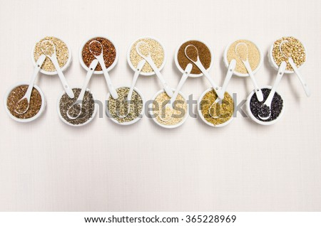 Ancient grains in white ceramic bowls with spoons, a healthy gluten free alternative - stock photo