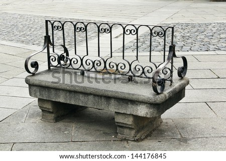 ancient granite bench seating and wrought iron backing - stock photo