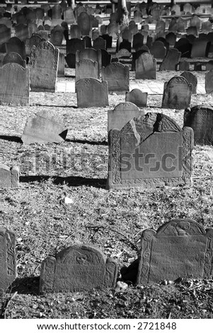 ancient grave stones in black and white in bright sun light on a beautiful winter's day, portrait - stock photo