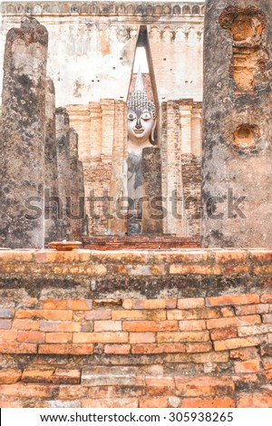 """Ancient Great Buddha Statue Behind the Wall, Sukhothai Style Architecture. At """"Wat Si Chum"""" in Sukhothai Historical Park, Sukhothai Province, Thailand. - stock photo"""